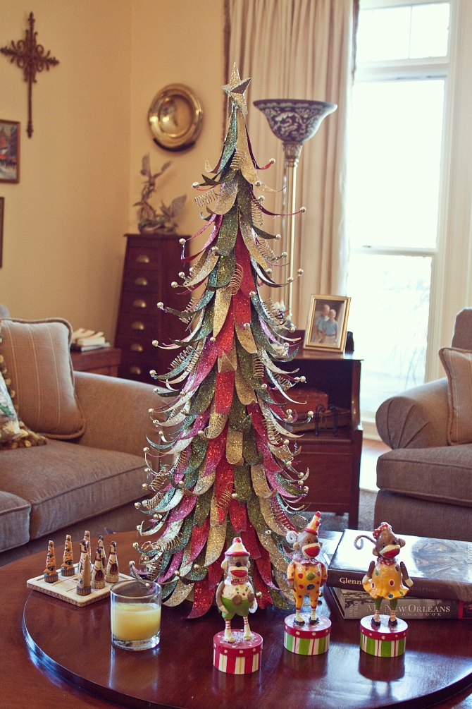 In the living room, this colorful table top tree is surrounded by jolly sock monkeys.